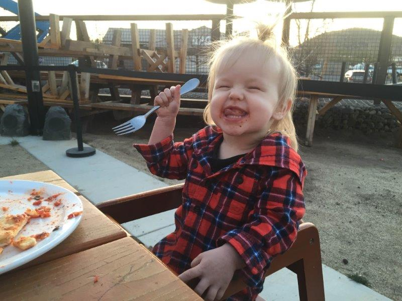 Lily enjoying her dinner at Worthy with the biggest cheese face!