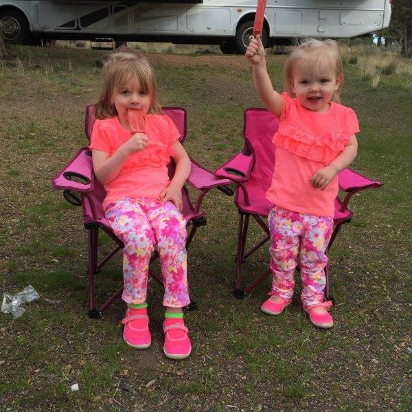 Matching sisters enjoying messy popsicles.